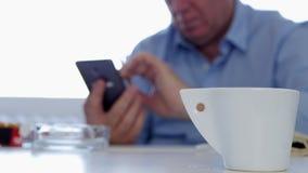 Uomo d'affari Smoke un caffè e un testo della bevanda della sigaretta facendo uso del cellulare nella pausa del lavoro video d archivio