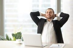 Uomo d'affari soddisfatto che si rilassa nel luogo di lavoro Fotografia Stock