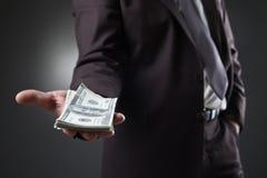 Uomo d'affari in soldi della tenuta del vestito su buio Fotografia Stock
