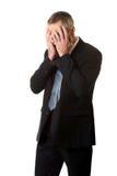 Uomo d'affari sollecitato che copre il suo fronte di mani Fotografia Stock Libera da Diritti