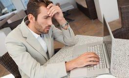 Uomo d'affari sollecitato che lavora con il suo computer portatile alla tavola Fotografie Stock Libere da Diritti