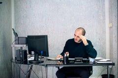 Uomo d'affari sollecitato che lavora nel suo ufficio fotografie stock