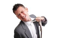 Uomo d'affari sollecitato che strappa suo legame fuori fotografia stock libera da diritti