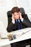 Uomo d'affari sollecitato che tiene la suoi testa e preoccuparsi immagine stock libera da diritti
