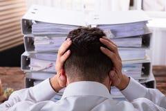 Uomo d'affari sollecitato In Front Of Stacked Folders immagine stock