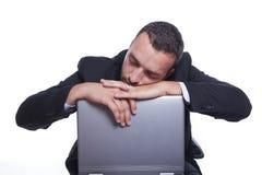 Uomo d'affari sonnolento con il suo computer portatile che cattura rottura fotografia stock