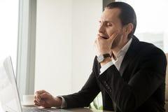 Uomo d'affari sonnolento stanco che sbadiglia davanti al computer portatile nel luogo di lavoro immagine stock libera da diritti
