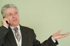 Uomo d'affari sorpreso che comunica sul telefono Fotografia Stock
