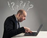 Uomo d'affari sorpreso che esamina il suo computer portatile Immagine Stock Libera da Diritti