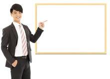 Uomo d'affari sorridente asiatico che indica bordo in bianco fotografia stock