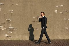 Uomo d'affari sorridente che cammina e che parla sul telefono cellulare Immagine Stock Libera da Diritti