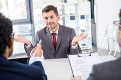 Uomo d'affari sorridente che gesturing durante l'intervista di lavoro Immagini Stock