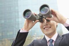 Uomo d'affari sorridente che guarda tramite il binocolo, riflessione blu nel vetro Fotografia Stock