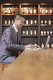 Uomo d'affari sorridente che lavora al computer portatile, scaffale del vino nei precedenti Fotografie Stock