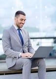 Uomo d'affari sorridente che lavora con il computer portatile all'aperto Fotografia Stock Libera da Diritti