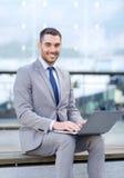 Uomo d'affari sorridente che lavora con il computer portatile all'aperto Immagine Stock
