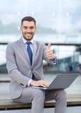 Uomo d'affari sorridente che lavora con il computer portatile all'aperto Fotografia Stock