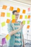 Uomo d'affari sorridente che legge le note appiccicose sulla parete di vetro in ufficio creativo fotografia stock