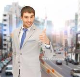 Uomo d'affari sorridente che mostra i pollici su Fotografia Stock