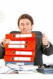 Uomo d'affari sorridente che osserva fuori dai dispositivi di piegatura Immagini Stock Libere da Diritti