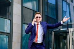 Uomo d'affari sorridente che parla sul telefono e che accoglie Fotografie Stock