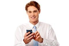 Uomo d'affari sorridente che per mezzo del telefono cellulare Fotografie Stock