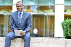 Uomo d'affari sorridente che per mezzo della compressa fotografia stock