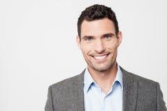 Uomo d'affari sorridente che posa alla macchina fotografica Fotografia Stock