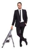 Uomo d'affari sorridente che si appoggia scala a libro Immagini Stock
