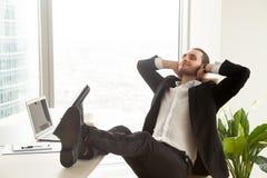 Uomo d'affari sorridente che si rilassa nel luogo di lavoro in ufficio moderno Fotografia Stock Libera da Diritti