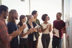 Uomo d'affari sorridente che spiega al gruppo creativo all'ufficio immagine stock libera da diritti