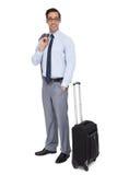 Uomo d'affari sorridente che sta accanto ai suoi bagagli Immagini Stock
