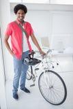 Uomo d'affari sorridente che sta con la sua bici Fotografia Stock
