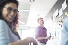 Uomo d'affari sorridente con il collega femminile in priorità alta all'ufficio creativo immagine stock libera da diritti