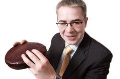 Uomo d'affari sorridente con il grafico a torta del cioccolato in mani fotografie stock libere da diritti