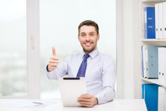 Uomo d'affari sorridente con il pc ed i documenti della compressa Fotografia Stock Libera da Diritti