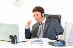 Uomo d'affari sorridente con la cuffia avricolare che si siede allo scrittorio Immagini Stock