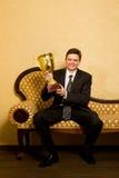 Uomo d'affari sorridente con la tazza di vittoria a disposizione sul sofà Fotografia Stock