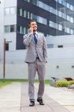 Uomo d'affari sorridente con lo smartphone all'aperto Fotografie Stock