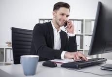 Uomo d'affari sorridente con una battitura a macchina dello smartphone Immagini Stock