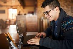 Uomo d'affari sorridente delle free lance che lavora al computer portatile in caffè Uomo di blogger che aggiorna il suo profilo n Fotografia Stock
