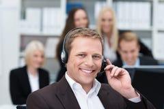 Uomo d'affari sorridente facendo uso di una cuffia avricolare Immagine Stock