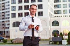 Uomo d'affari sorridente felice che per mezzo dello smartphone moderno vicino all'ufficio al primo mattino fotografia stock libera da diritti