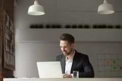 Uomo d'affari sorridente felice in ufficio che esamina lo schermo del computer portatile Fotografia Stock Libera da Diritti