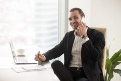 Uomo d'affari sorridente felice in ufficio moderno che parla sul cellulare Fotografia Stock Libera da Diritti