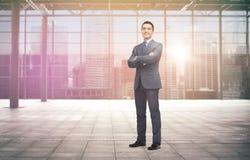 Uomo d'affari sorridente sopra il corridoio e la città vuoti Fotografie Stock