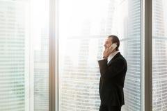 Uomo d'affari sorridente in vestito costoso che parla sul cellulare dentro di Immagine Stock Libera da Diritti