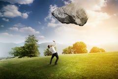 Uomo d'affari sotto la grande pietra di volo sopra paesaggio luminoso immagini stock