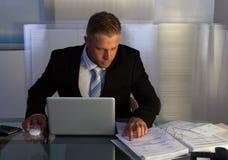 Uomo d'affari sotto pressione che lavora fuori orario fotografia stock libera da diritti