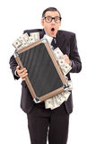 Uomo d'affari spaventato che giudica una borsa piena di soldi Immagine Stock Libera da Diritti